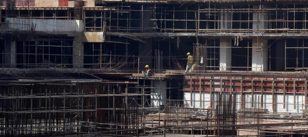 Construction workers work on a site of a residential building in Mumbai